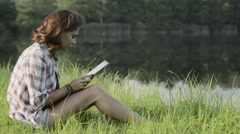 Young woman seated on grass take photo with tablet on lake shore Stock Footage