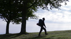 Young man silhouette walking in nature enjoying the panorama - stock footage