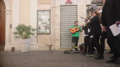 Band marching in front of a Street Musician with Puppet in Grosseto, Italy Stock Footage