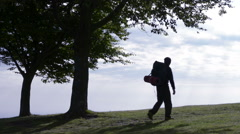 Young man silhouette walking in nature take a rest enjoying the panorama Stock Footage