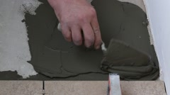 Man applying ceramic tile to a floor, close up Stock Footage