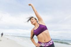 Young fit female stretching and heating up before outdoor workout - stock photo
