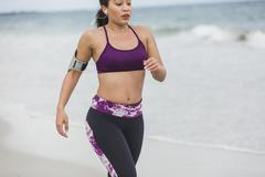Fitness Woman finishing work out by the Ocean at cloudy winter day Stock Photos