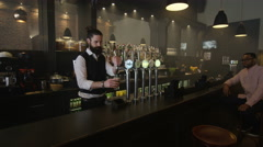 4K Friendly bartender serving & chatting with lone customer in trendy bar Stock Footage