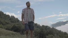 Young man in summer day is trekking outdoor on mountain path  slow motion Stock Footage