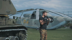 Muscular man in a military uniform has arranged training at a military base Stock Footage