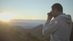 Young man in nature mountain outdoor shoot photos with camera at sunrise Stock Footage