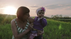 The little daughter sitting on the lap of the mother at sunset. Stock Footage