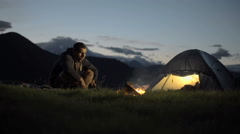 Young man warming with camp fire in nature mountain outdoor camping scene Stock Footage