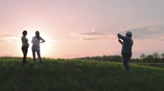 The man is photographing two pregnant women against the background of a pink sun Stock Footage