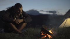 Young man warming with camp fire in nature mountain outdoor Stock Footage