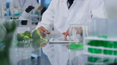 4K Food science researchers in lab, 1 man injecting chemicals into broccolli Stock Footage