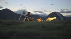 Group of three friends warming with camp fire in nature mountain outdoor - stock footage