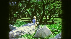 1964: Spoiled brat kid catching insects on green manicured garden lawn. Stock Footage