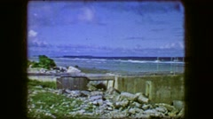 1944: Concrete embankment ruins blue sky ocean beach exposed rocky surf. Stock Footage