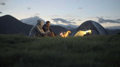 Group of three friends warming with camp fire in nature mountain - stock footage