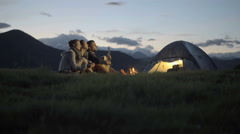 Group of three friends play guitar and sing at camp fire in nature mountain Stock Footage
