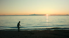 Man Skipping Rock into Ocean Sunset Stock Footage