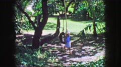 1964: Young boy plays on rope tire swing hot summer day in forest lawn shade. Stock Footage
