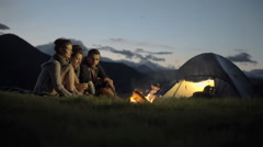 Group of three friends talking, smiling and warming with camp fire in nature - stock footage