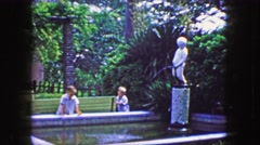 1944: Little boy peeing fountain statue in fancy outdoor home garden. Stock Footage