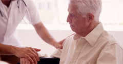 Male doctor consoling to a senior patient Stock Footage