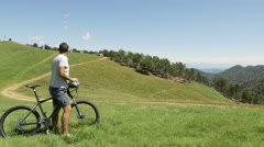 Young man with mountain bike looking mountain panorama in outdoor Stock Footage