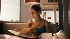 The girl in the cafe menu looks Stock Footage