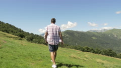 Back and side view of young man hiking in mountain outdoor nature scenery Stock Footage