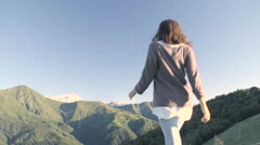 Back view of young woman hiking away in mountain outdoor nature scenery Stock Footage