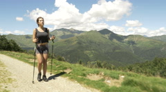Front view of young woman doing nordic walking sport in nature outdoor Stock Footage