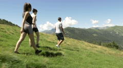 Back and side view of young friends hiking and looking around in mountain Stock Footage