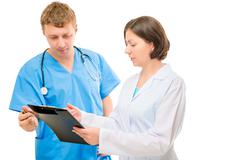Couple of doctors discussing a diagnosis written in the folder Stock Photos