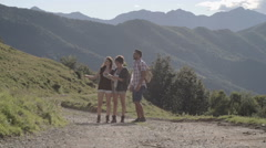 Young friends hiking toward camera on a road and checking map Stock Footage