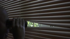 Man 30s looks and searches with binoculars and looks out  through the blinds Stock Footage