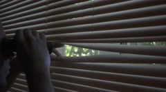 Man 30s looks and searches with binoculars and looks out  through the blinds - stock footage