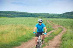 Cyclist on a white bicycle in a blue uniform rides Stock Photos