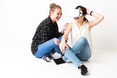 Cute teenagers playing with virtual reality headset - stock photo