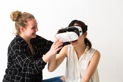 Smiling blonde girl looking at friend wearing virtual reality headset - stock photo