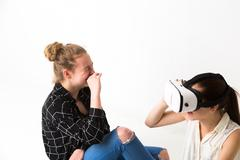 Laughing girl looking at friend wearing virtual reality headset Stock Photos