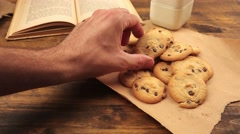 Man picking homemade american chocolate chip cookies on table Stock Footage