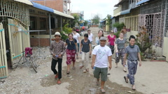 Youth Missions Team Walking Through Cambodian Slum Community Stock Footage