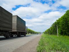 road with moving cars and green surroundings on the sides - stock photo