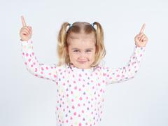 little girl wearing  pointing by forefinger to somewhere up - stock photo