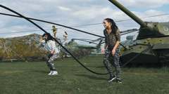 Two girls jumping on a military base on the ropes Stock Footage