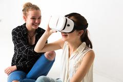Young and smiling teenagers playing with virtual reality headset - stock photo