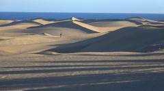 two people walking through the desert. - stock footage