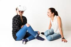 Young laughing girls playing with virtual reality headset - stock photo