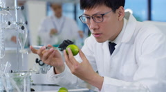 4K Food science researchers working in lab, 1 man injecting chemicals into lime Stock Footage