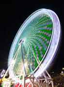 Amusement park attractions. Spinning ferris wheel at night. Motion blur Stock Photos